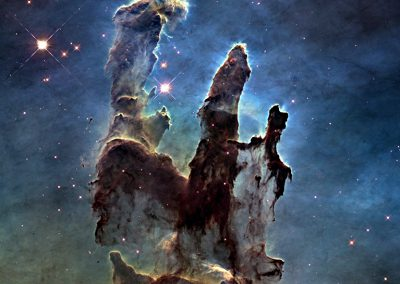 the multi-colored glow of the gas clouds, tendrils of dark cosmic dust, and the famous rust-colored pillars that are part of the Eagle Nebula