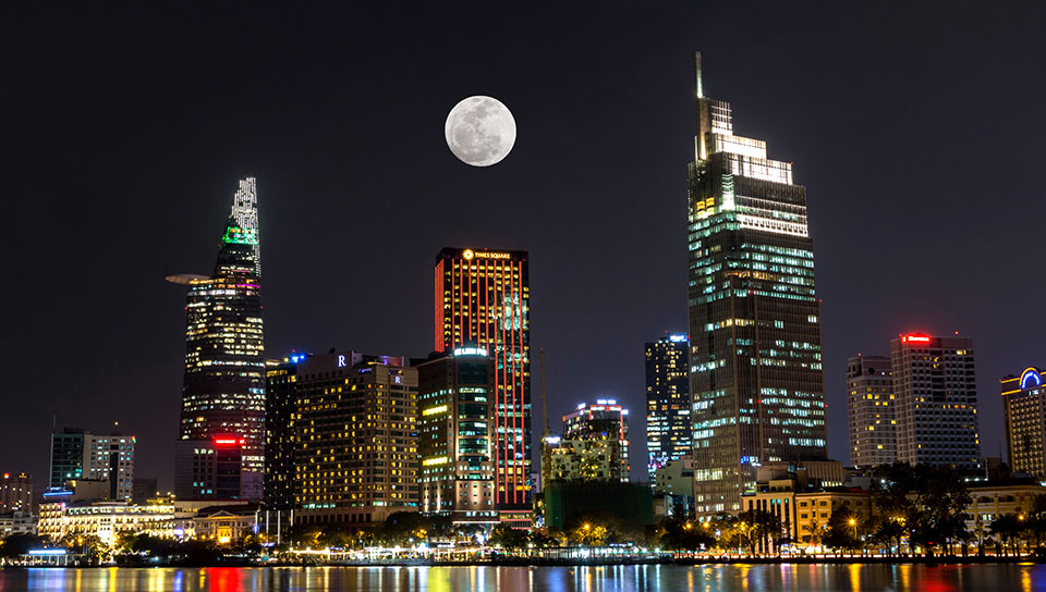 A city skyline at night with the moon above