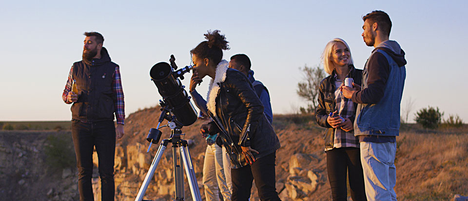 A group of friends conversing behind a telescope in an open field.