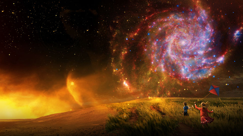 Two children in a field looking up at a spiral galaxy