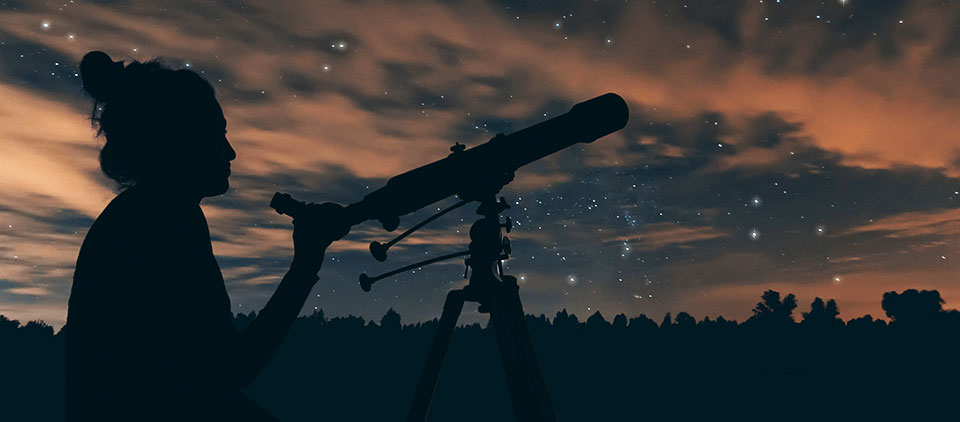 A woman and her telescope at dusk.