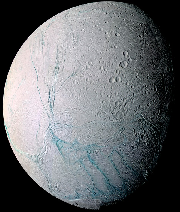 Enceladus appears covered in craters and cracks in this enhanced-color mosaic.