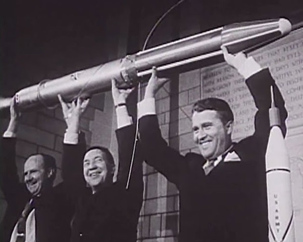 Three people holding a rocket overt their heads