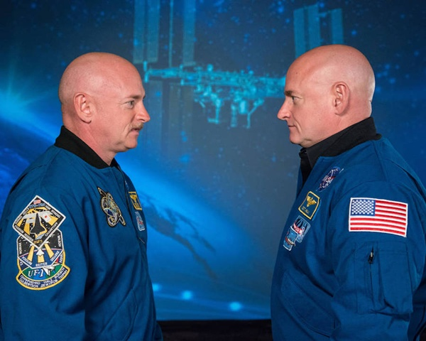 A picture of Mark Kelly and Scott Kelly wearing matching blue NASA jackets and looking each other in the eyes.