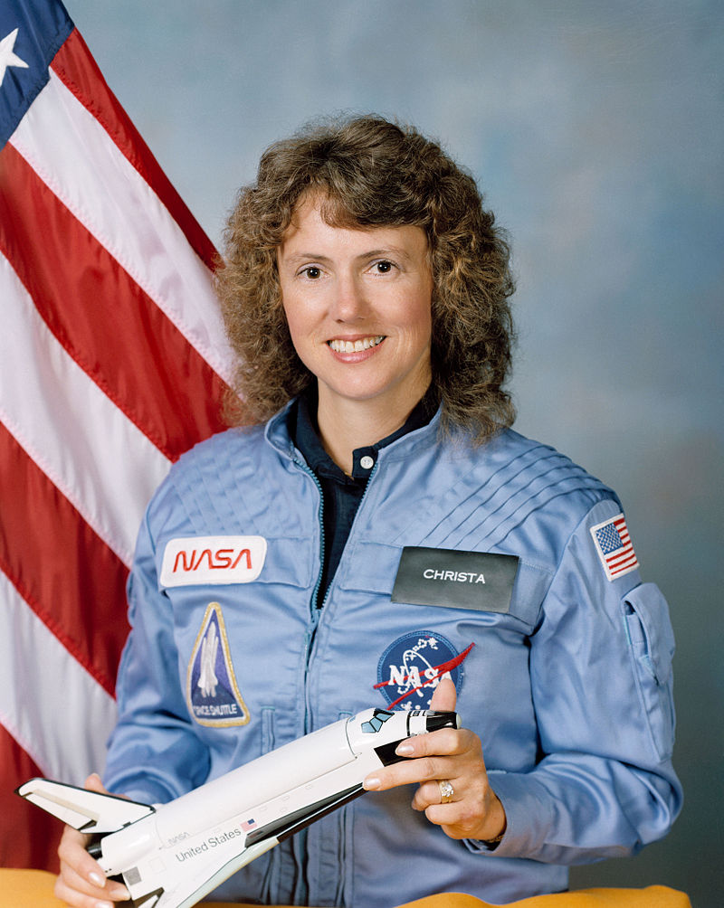 A headshot of Christa McAuliffe with an American flag in the background.