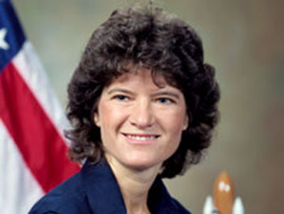 A headshot of Sally Ride in front of an American flag.