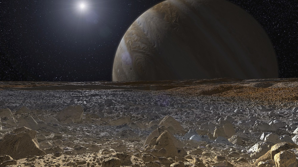 A picture of Europa's rocky surface with Jupiter and the Sun in the background.