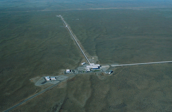 A bird's eye view of LIGO, which has two large physics observatories with two beam lines extending out of the observatories.