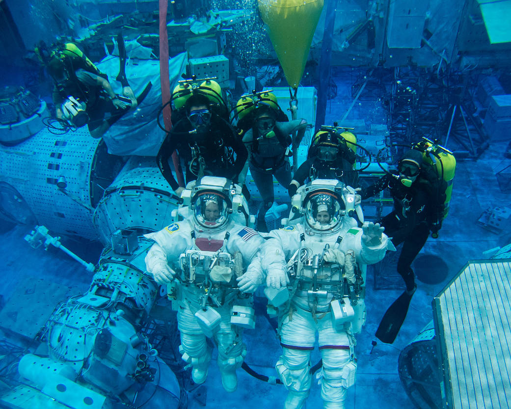 A picture of two NASA astronauts wearing spacesuits underwater.