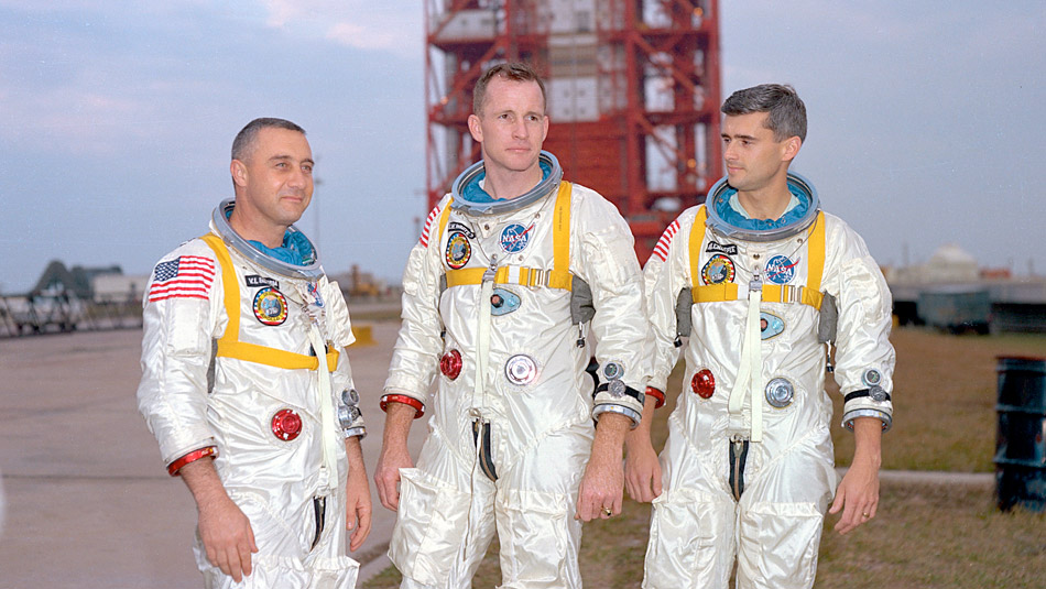Three astronauts standing side by side with a launchpad in the background