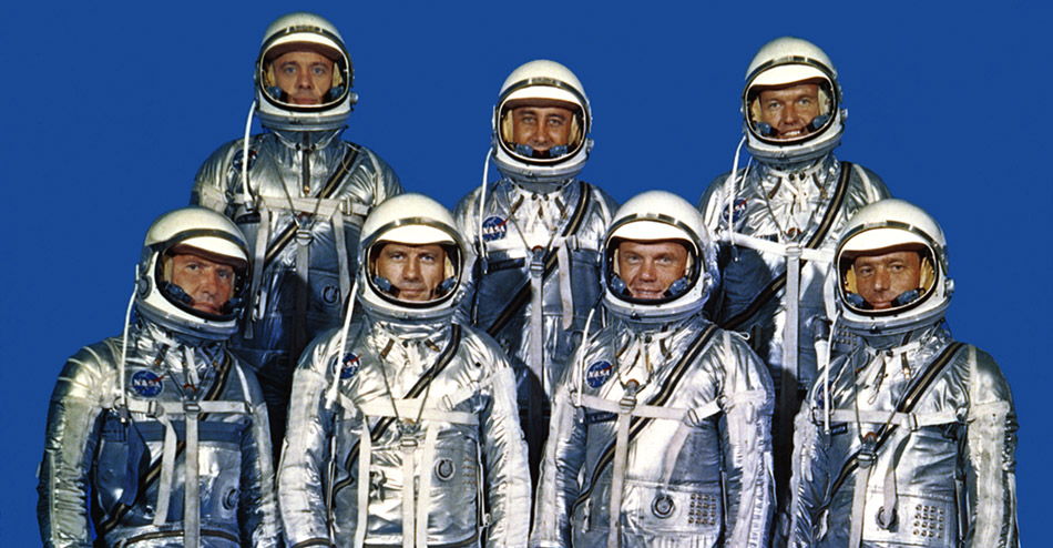 seven astronauts standing together in their space suits