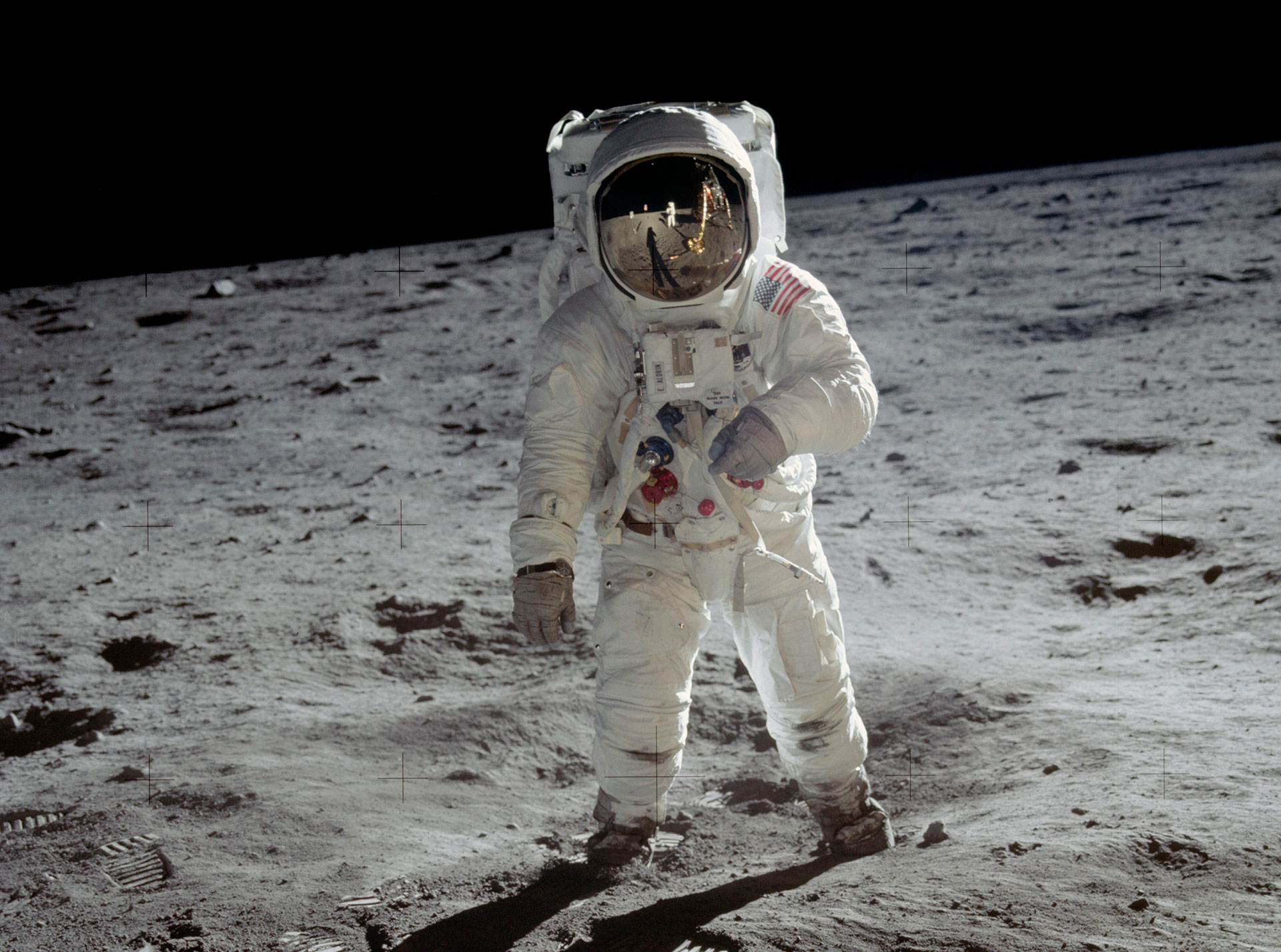 Astronaut Buzz Aldrin walks on the surface of the Moon.