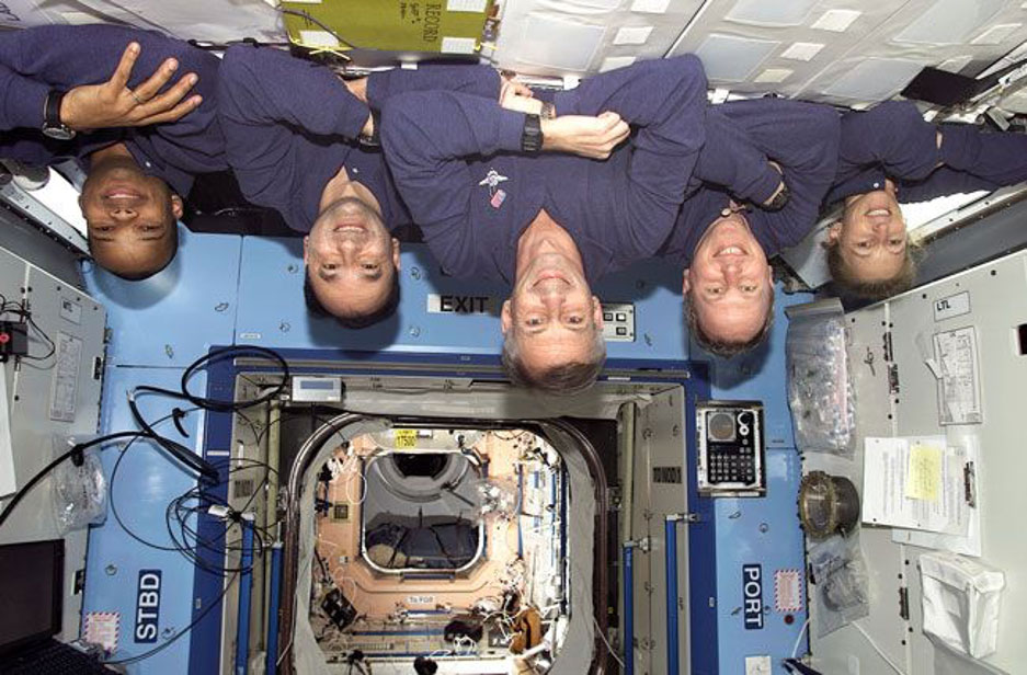 Four astronauts floating upside down.