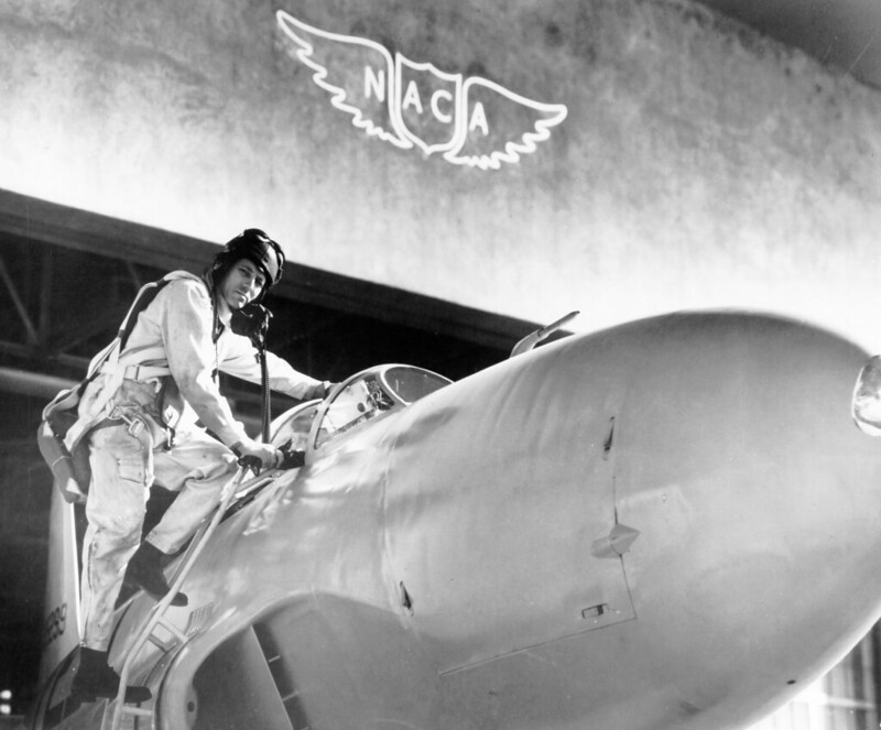 A test pilot climbs into an aircraft in front of a hanger showing the NACA logo