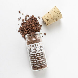 A vial of the simulated Mars soil with the simulant pouring out