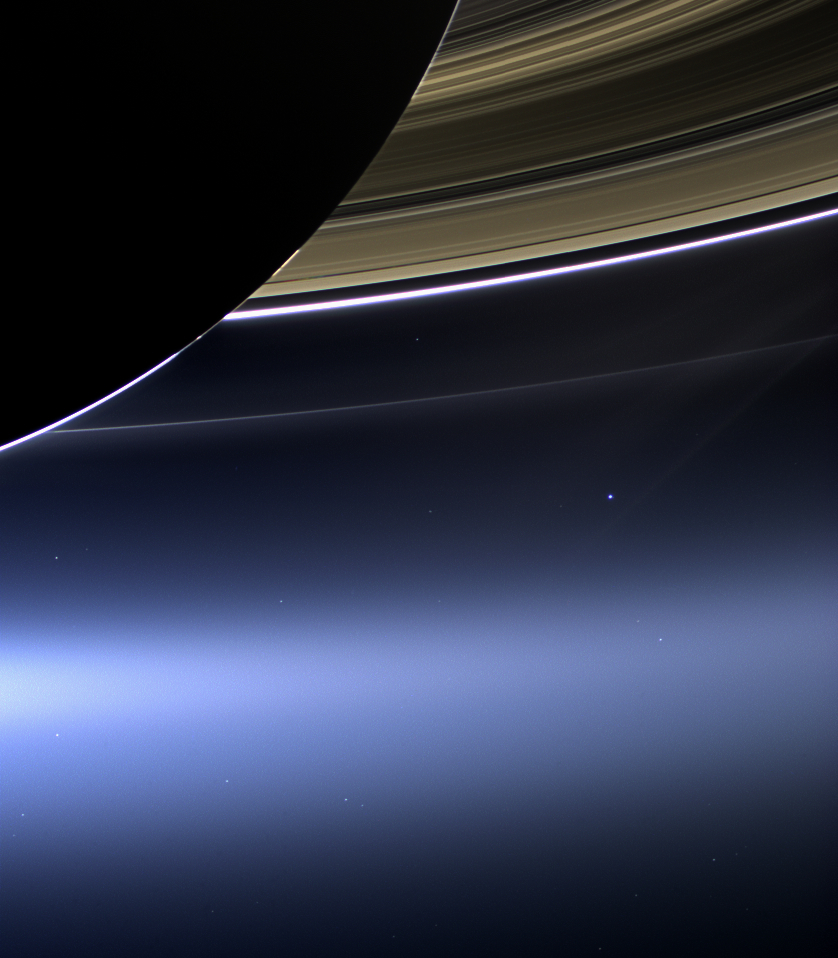 Saturn and its rings are in the foreground with a bright blue dot of Earth underneath the rings